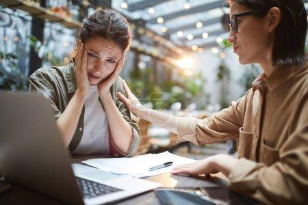 Photo pour Portrait d'une jeune femme frustrée travaillant à table dans un café avec un ami ou une collègue la réconfortant, espace de reproduction - image libre de droit