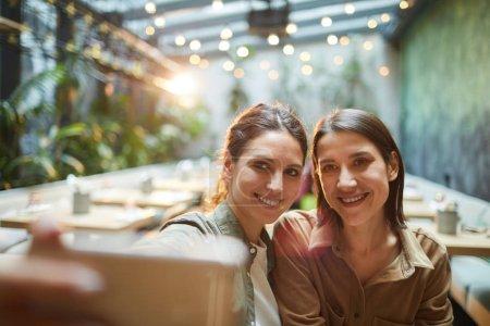 Photo pour Portrait de deux jeunes femmes souriant à la caméra du smartphone tout en prenant des photos selfie dans un café extérieur - image libre de droit