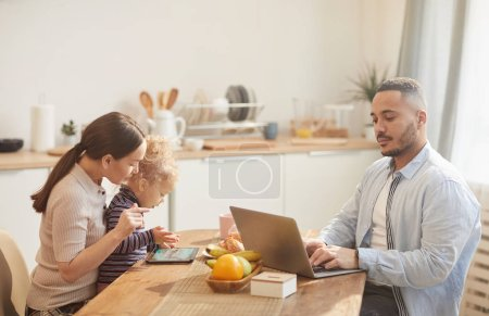Photo for Side view portrait of modern father using laptop while enjoying family breakfast in cozy kitchen interior - Royalty Free Image