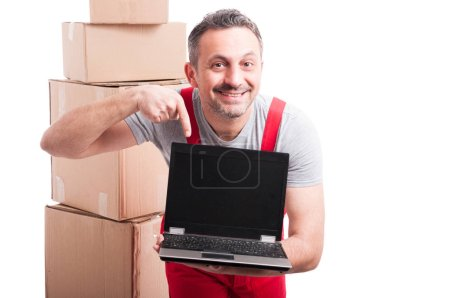 Mover guy holding and pointing blank screen laptop