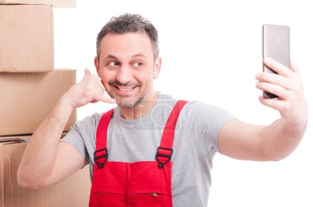 Mover guy making calling gesture taking selfie and smiling