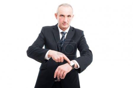 Senior elegant man showing time on wrist watch wea...