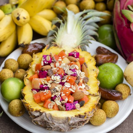 Photo for Fresh tropical fruit salad in pineapple with oat flakes, raisins, nuts, sesame and mix sliced fruits ( dragon fruit, pineapple, banana, mango, papaya) - healthy breakfast. Thailand, close up - Royalty Free Image