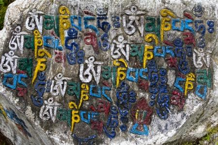Photo for Prayer stones as a form of prayer in Tibetan Buddhism, on the hill in Himalaya mountains. Mcleod Ganj, Dharamsala, India. Close up - Royalty Free Image