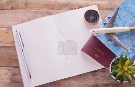 Blank notebook,passport,compass,airplane and map on wooden table