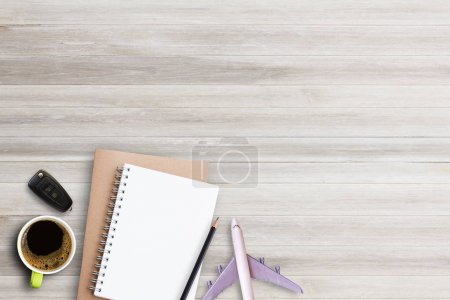 Notebook,pencil with cup of coffee,car key and airplane on white