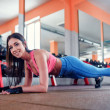 Young sporty girl makes plank exercise in the gym...