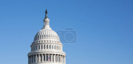 A close up view of The Capitol Building rotunda in Washington, D.C. on a beautiful day with a bright blue sky.