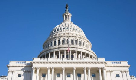 Close up view of the back of the Capitol Building rotunda in Washington, D.C. on a beautiful day with a bright blue sky.