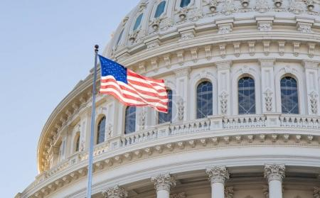 A close up view of The Capitol Building rotunda in Washington, D.C. with an American Flag flying proudly.