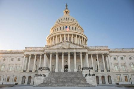 Wide angle view of the front of the Capitol Building in Washington, D.C. on a beautiful day with a blue sky.
