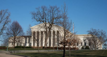 The Supreme Court building in Washington, D.C. on a winter day with bright blue sky and bare trees.