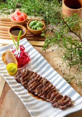 japanese food wafu steak served on white plate with soy sauce