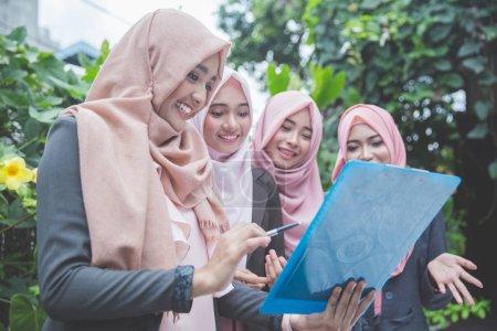 Photo pour Groupe de quatre jeunes femmes d'affaires musulmanes ayant une réunion en plein air - image libre de droit