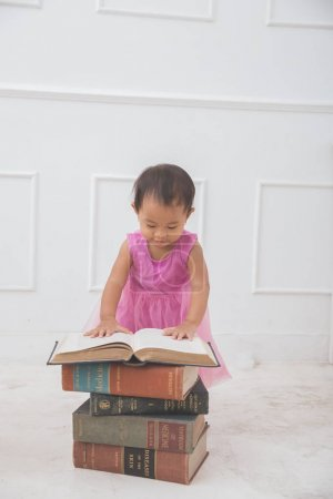 Curious baby girl reading a book