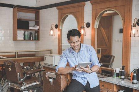 man in barbershop with digital tablet