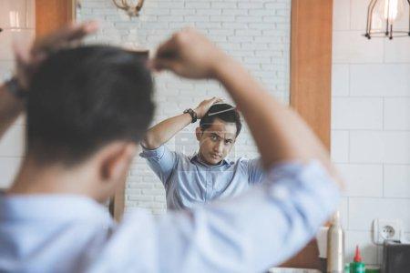 Photo pour Portrait de l'homme peignant ses cheveux après avoir été coupé au salon de coiffure - image libre de droit