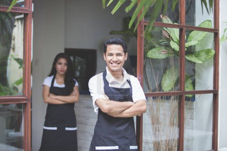 Male waitress standing with arms crossed in cafe