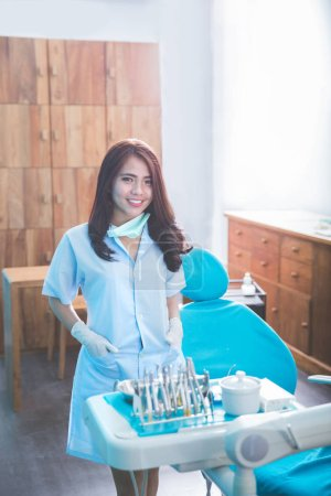 female dentist with tools over medical office clinic