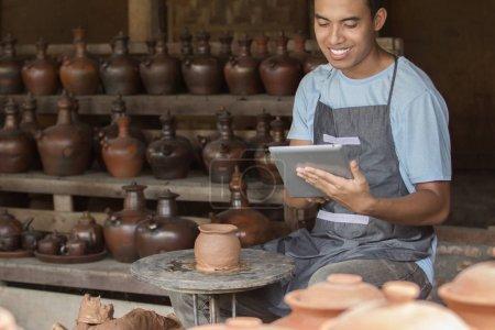 male potter using digital tablet
