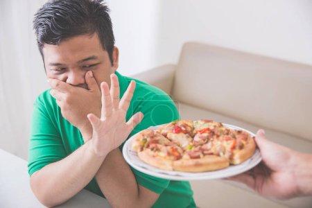 Photo pour Portrait d'un homme fermant la bouche avec la main refusant la nourriture tandis que quelqu'un lui offrant une pizza - image libre de droit