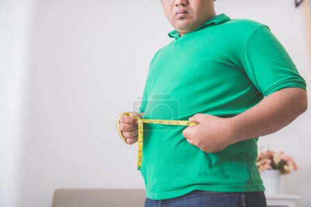 overweight man measuring his belly at home