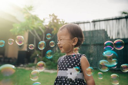 little girl trying to catch soap bubbles
