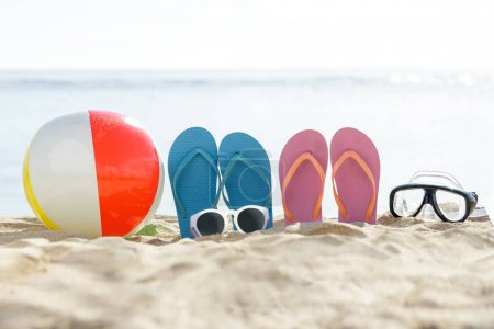 flipflops, beach ball, sunglasses, and snorkel on the sand