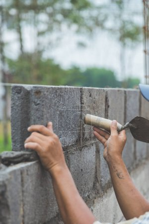 bricklayer with trowel installing cement bricks