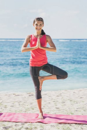 beautiful fit woman standing in one foot doing yoga pose