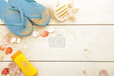 blue flipflops, sunblock, and seashells