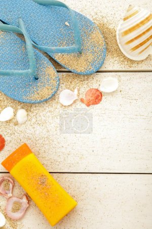 blue flipflops, sunblock, and seashells on white wooden table