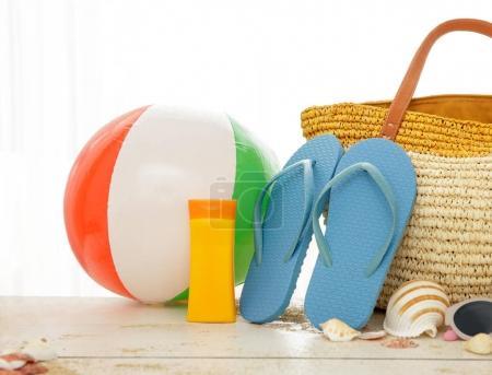 beach ball, sunblock, flipflops and bag