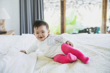asian baby lying on bed