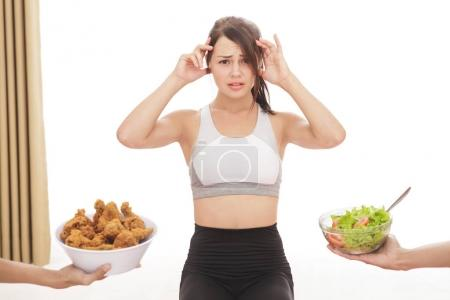 sporty girl confuse to choose a meal on diet process