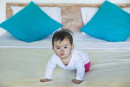 girl crawling on bed