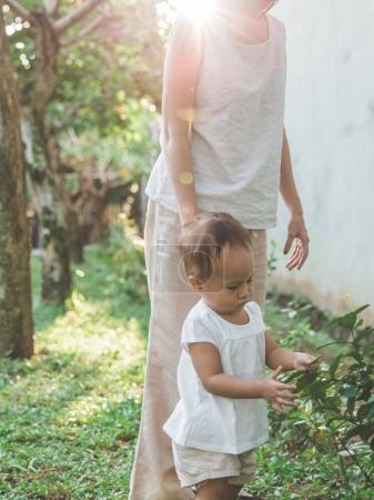 mother with kid interested in plant