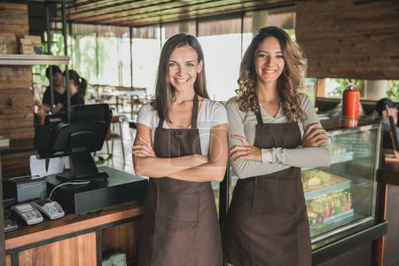 two beautiful female cafe owner smiling proudly