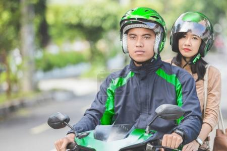 motorcycle taxi driver taking passenger