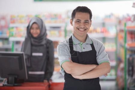 supermarket owner smiling to camera