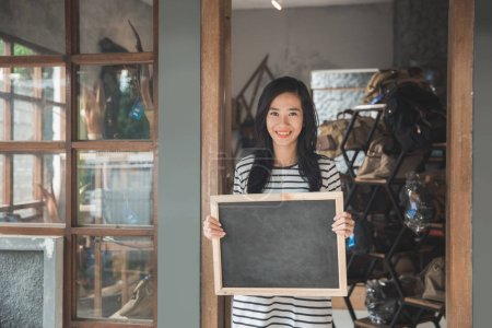 business owner holding a blackboard