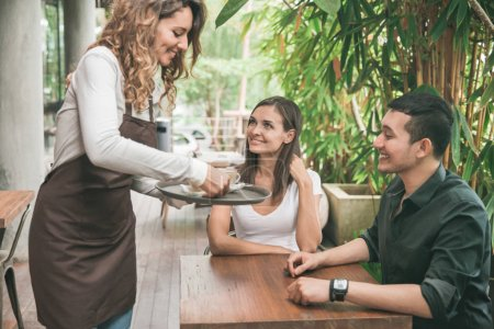 Photo for Portrait of a female waitress serving coffee to a couple customer - Royalty Free Image