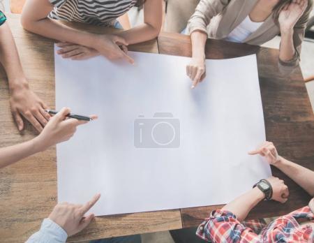 Photo pour Équipe d'affaires pointant leur plan sur le papier blanc sur la réunion - image libre de droit