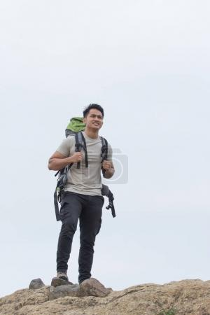 Hiker with backpack smiling on peak