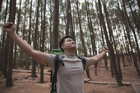 Hiker raising his arms in forest