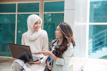 students using laptop on campus