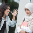 Portrait of female student yelling at her friend o...