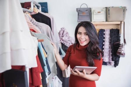 Photo pour Démarrage d'entreprise. Belle jeune femme asiatique à l'aide de tablette numérique sourire en se tenant debout dans le magasin de vêtements - image libre de droit