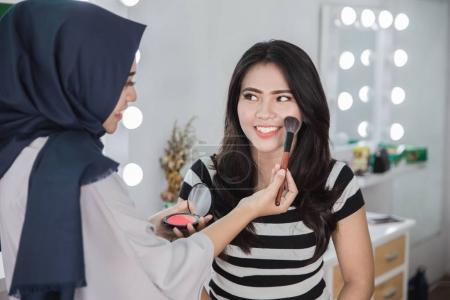 make up artist applying makeup