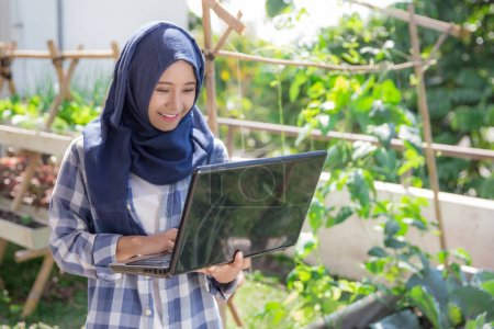 attractive muslim woman with laptop in the farm